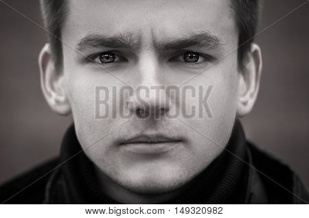Black and white portrait photo of young man with sad look
