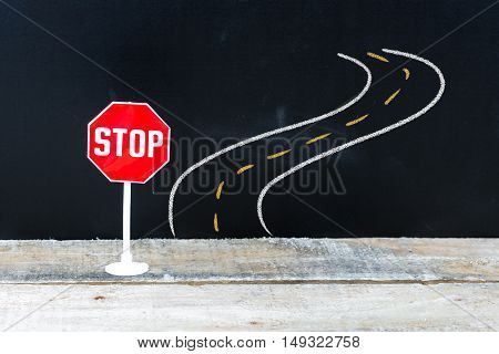 Mini Stop Sign In Front Of Curved Road, Hand Drawing Over Chalkboard