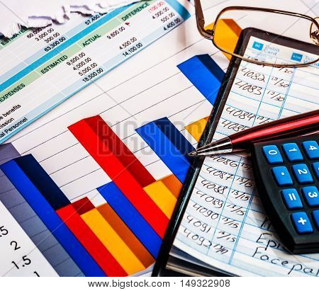Business graphics and checkbook with pen and glasses