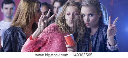 Two girls posing to the common photo during the students' party