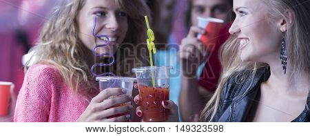 Shot of young women smiling to each other with drinks in their hands