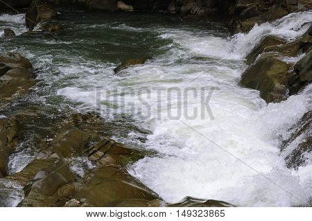Streaming water flow on the rocky rapids of Prut river