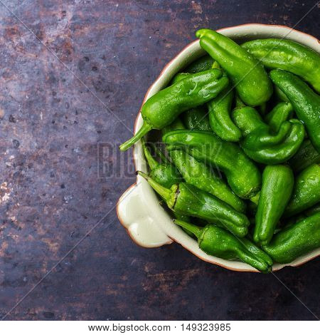 Food and drink, still life, moody concept. Raw green peppers pimientos de padron mexican jalapeno traditional spanish tapas on a black rusty table. Selective focus top view flat lay, copy space
