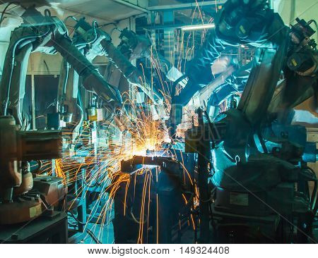 Team Robots welding movement in a car production factory