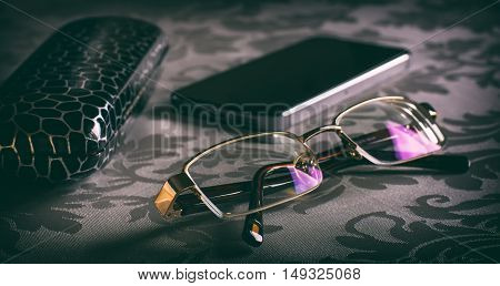 Glasses on the table and spectacle-case. Toned image. Selective focus