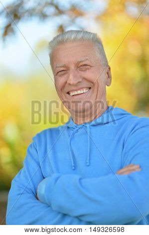 Happy elderly man enjoying in autumn park