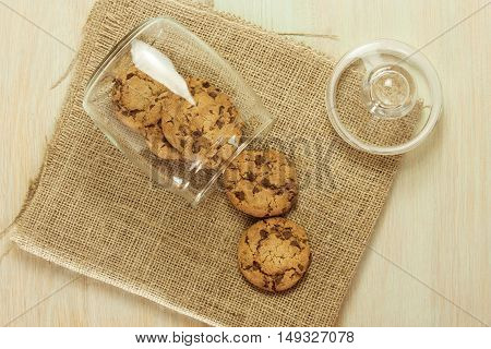 A photo of an open glass jar of chocolate chips cookies on a burlap texture, shot from above