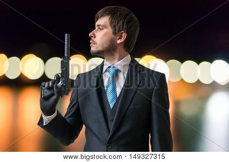 Agent Or Spy Holds Gun With Silencer In Hand At Night.