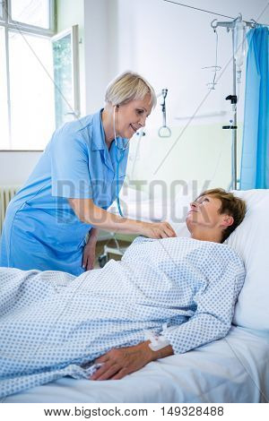 Nurse examining a patient with a stethoscope in hospital ward