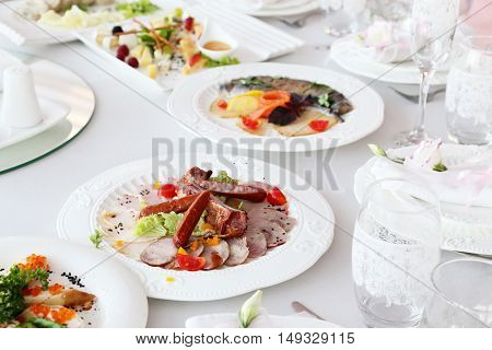 Meat cold cuts sausages on a banquet table