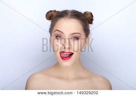 Portrait Of A Young Pretty Woman With Trendy Makeup Bright Red Lips Funny Bun Hairstyle And Bare Sho