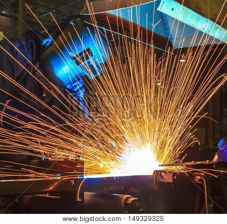 worker with protective mask welding metal. in Industrial automotive part. in car production factory. with fire spark
