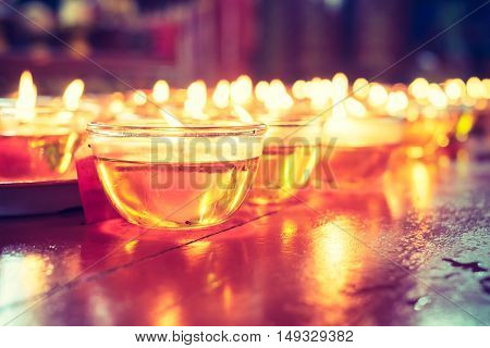 Pray candle glass on wood table in chinese temple.