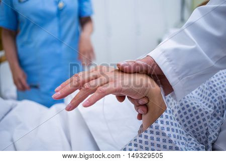 Doctor examining patients pulse in hospital room