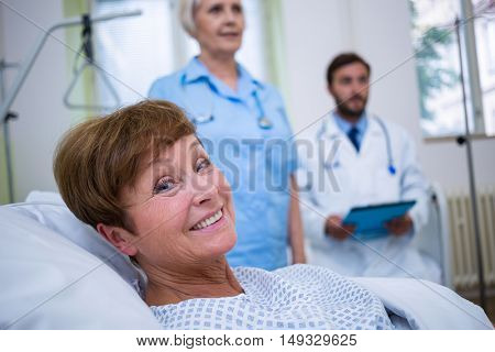 Portrait of smiling patient lying on bed in hospital room
