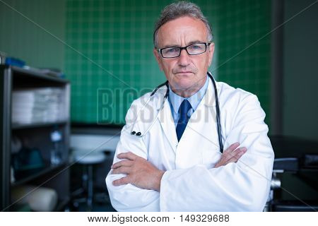 Portrait of doctor standing with arms crossed in hospital