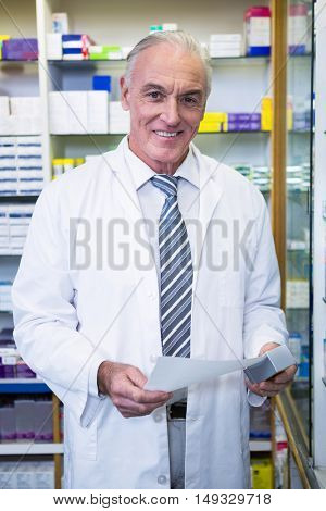 Portrait of pharmacist holding a prescription and medicine in pharmacy