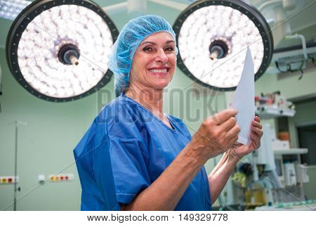 Portrait of smiling surgeon holding report in operation room at hospital