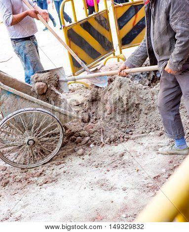man dig dirt at construction site at road