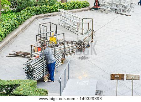 worker keep metal pipe in front of building.