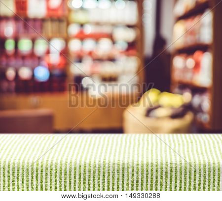 Table With Green Pattern Tablecloth With Blur Cafe Background,mock Up For Display Of Product