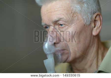 Close-up portrait of an elder man making inhalation