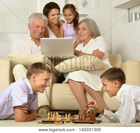 Happy family with kids on couch in living room with laptop