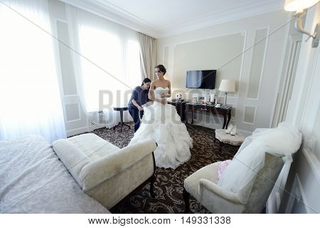 Bridesmaid is lacing white wedding dress for beautiful bride. Beauty model girl in bridal gown for marriage. Female portrait. Woman with curly hair and lace veil. Cute lady indoors