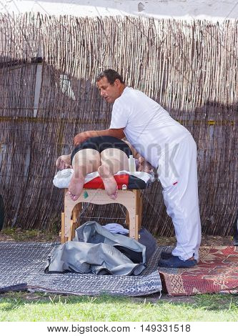 Tiberias Israel September 27 2016: Professionl masseur doing massage for the woman on the beach in Tiberias Israel