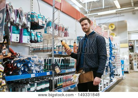 Young handyman shopping in a hardware store standing looking down at the camera with a product in his hand with a smile