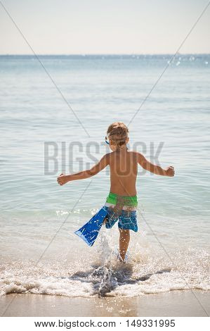 Happy boy in flippers running into ocean on a sunny day. Child going to swim in the sea. Vacations. Activities for child on the beach. Joy and happiness.