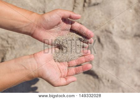 Sand running through female hands.Young woman with sand in her hands.