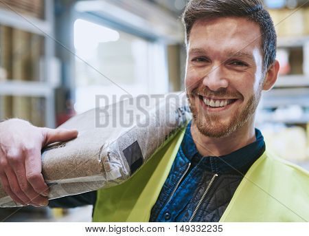 Smiling happy handsome young handyman or warehouse worker with a bag of product over his shoulder grinning at the camera close up view