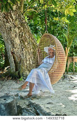 Happy elderly woman sitting on a swing at summer beach