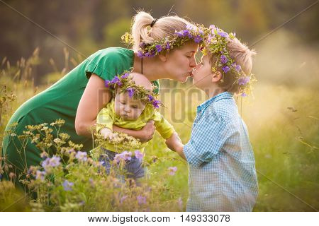 Happy family with two boys on a summer meadow. Mother with adorable kid boy and cute baby in flower wreath. Family together parent with little children. Woman kissing children on sunny day.