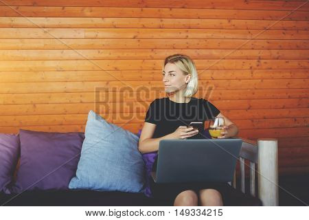 Hipster girl is looking on her friends while is sitting with mobile phone and laptop computer in cafe. Woman is waiting for a call on cell telephone from client after read her message on net-book