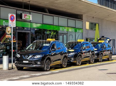 Wallisellen, Switzerland - 7 July, 2016: taxi cars with UBS Paymit application promotion. UBS Paymit application allows to send request and receive money using a smartphone.
