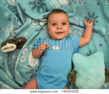 Surprised funny baby on a blue background