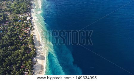 Top view aerial drone photo of stunning colored sea beach with crystalline water fringed with swaying tropical palms and leafy trees. Incredibly beautiful blue ocean meet with powder-white seashore