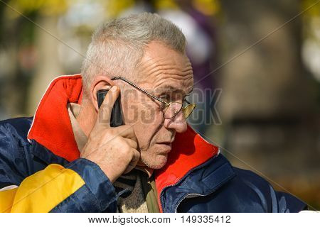Good looking active senior concentrated on important news during phone call in bright suuny autumn day close up view