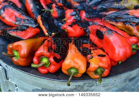 Preparing food for winter red peppers roasting on metal sheet cooker close up view