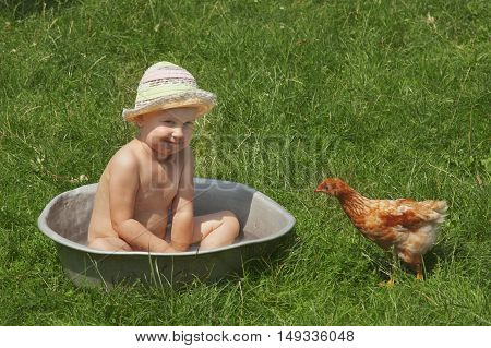 beautiful baby girl bathing outdoors and having fun with chickens