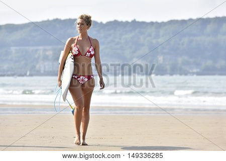 Surfer girl walking on a sandy beach with surfboard