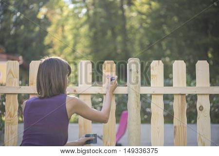 Woman varnishing a wooden picket fence outdoors in her garden in summer retro faded effect with copy space.