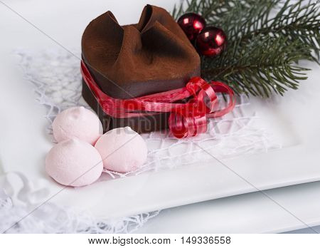 Chocolate dessert on a white plate with a Christmas tree and red balls