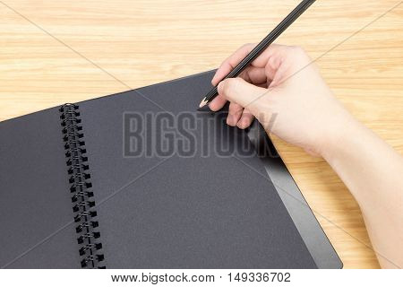 hand holding pencil writing on blank black book with table and business card on wooden table Mock up for adding your content.
