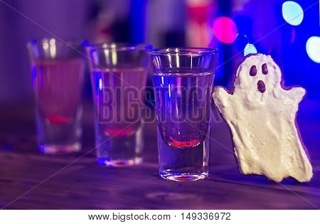 Halloween party. bloody cocktail and cookie in a form of goast. selective focus