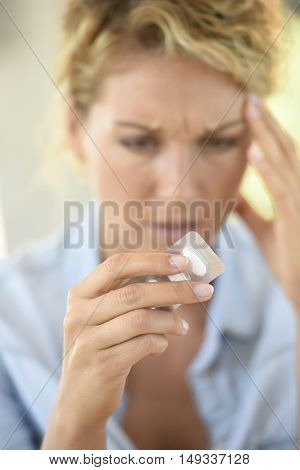 Woman taking pill to ease headache