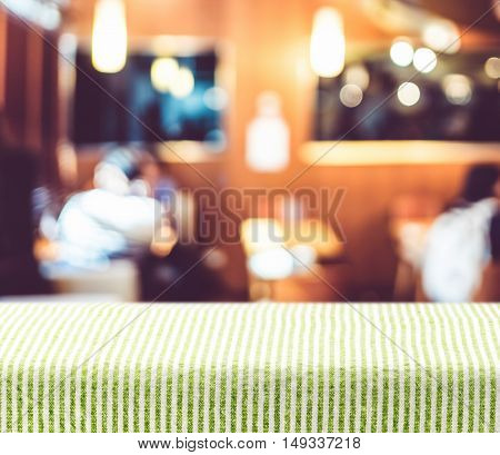 Table With Green Pattern Tablecloth With Blur Restaurant Background,mock Up For Display Of Product