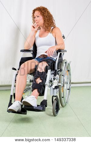 Disinterested Woman In Wheelchair With Hand To Lip